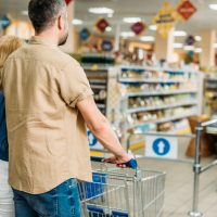 couple with shopping cart shopping together in grocery shop