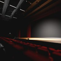 Theatre with empty stage in spotlight. Red theater curtain and seats